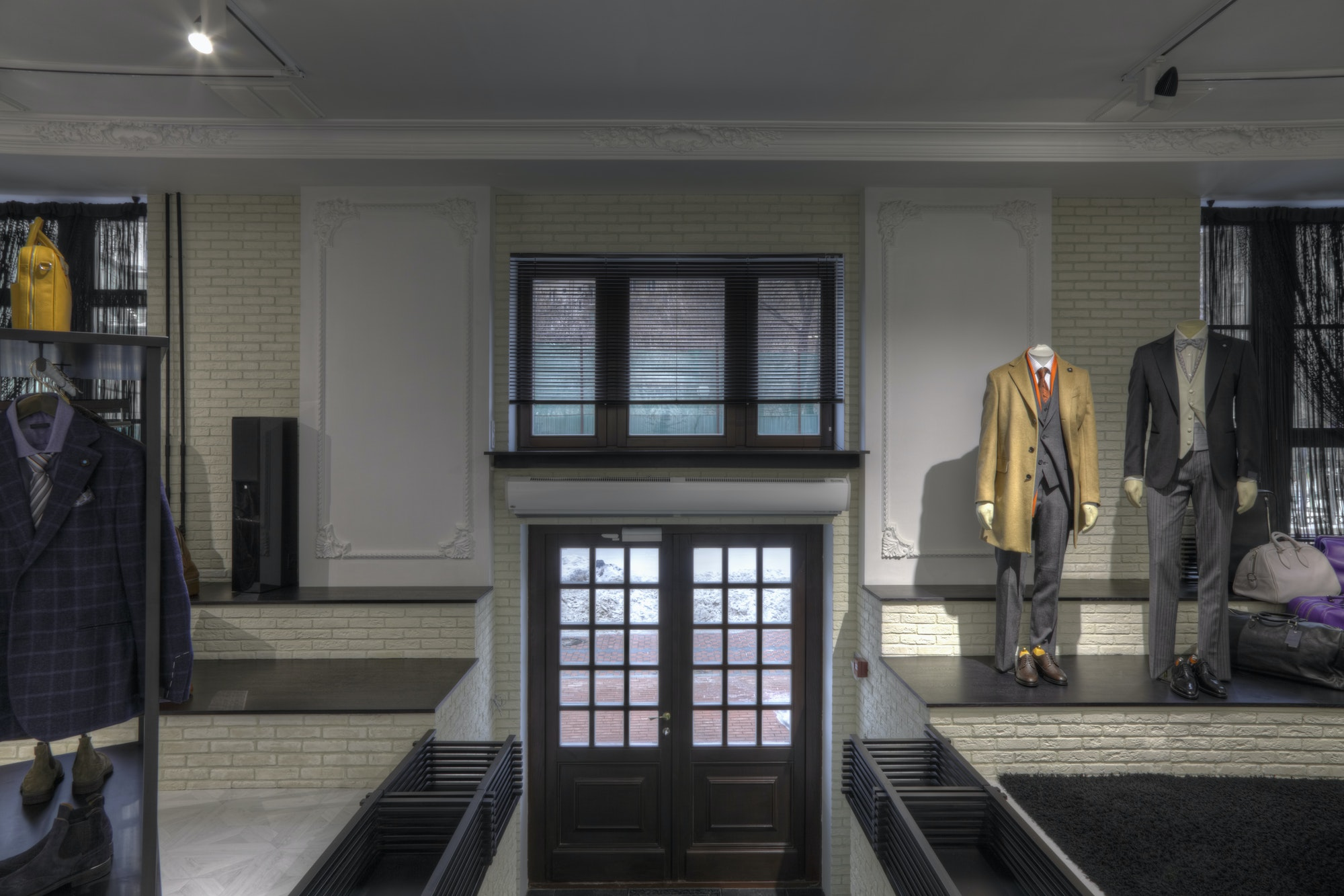 Suits on mannequins near doorway of clothing store for men
